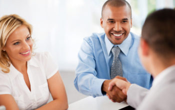 Successful group of businesspeople making a business deal. The two businessmen are shaking hands.  The focus is on the African-American man.   [url=http://www.istockphoto.com/search/lightbox/9786622][img]http://img543.imageshack.us/img543/9562/business.jpg[/img][/url]  [url=http://www.istockphoto.com/search/lightbox/9786738][img]http://img830.imageshack.us/img830/1561/groupsk.jpg[/img][/url]